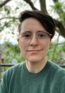 headshot of Caitlin wearing a green sweater